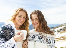 Two female friends enjoying hot drink In cafe at ski resort Royalty Free Stock Photos