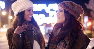 Two female friends enjoying a night on the town. Standing in a brightly lit street chatting in stylish winter outfits  panoramic view stock footage