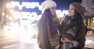 Two female friends enjoying a night on the town. Standing in a brightly lit street chatting in stylish winter outfits  panoramic view stock video