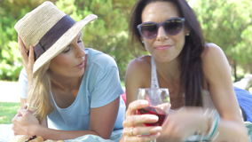 Two Female Friends Enjoying Picnic Together. Two women lying on grass facing camera chatting and drinking wine together.Shot on Canon 5d Mk2 with a frame rate of stock footage