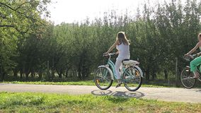 Two female friends enjoying summer vacation, riding bicycles in municipal park. Stock footage stock video footage