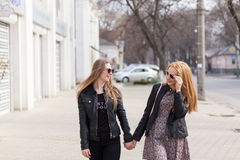 Two female friends enjoying a walk in sunny wheather Stock Image