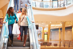 Two Female Friends On Escalator In Shopping Mall. Smiling At Each Other Royalty Free Stock Photo