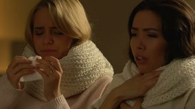 Two female friends with fever coughing and sneezing, seasonal cold, healthcare. Stock footage stock footage