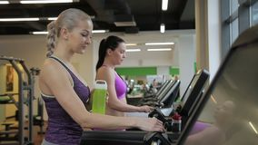 The two female friends are finishing their cardio training on the treadmills in the modern gym. The one lady has blond hair and wears dark sport top and the stock video