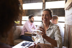 Two female friends having a drink at a table in a bar Royalty Free Stock Image