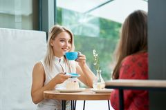 Two female friends having drinking coffee, talking. royalty free stock image
