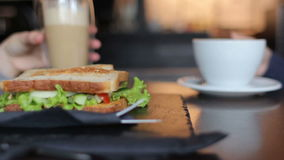Two female friends having lunch together. Drinking coffee eating sandwiches stock video footage