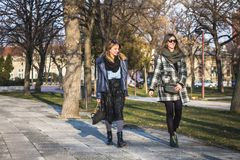 Two female friends having walk in the park stock image