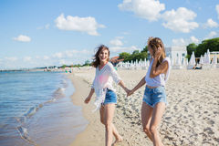 Two female friends holding hands walking on beach laughing stock photos
