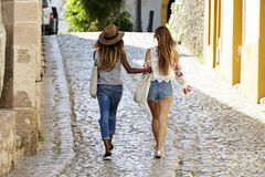Two female friends on holiday walking arm in arm, back view Stock Images