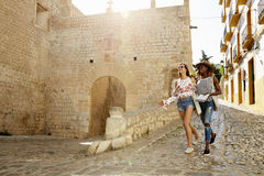 Two female friends on holiday walking with guidebook, Ibiza royalty free stock image