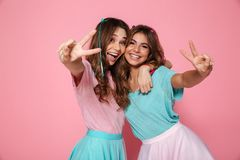 Two female friends hugging and having fun together, showing peace gesture while looking at camera royalty free stock photos