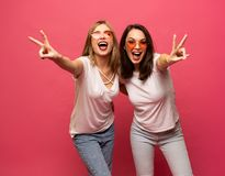 Two female friends hugging and having fun together, showing peace gesture while looking at camera, isolated over pink royalty free stock photography