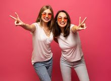 Two female friends hugging and having fun together, showing peace gesture while looking at camera, isolated over pink stock photo
