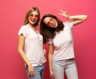 Two female friends hugging and having fun together, showing peace gesture while looking at camera, isolated over pink stock photography