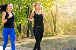 Two female friends jogging together in a park Royalty Free Stock Photo