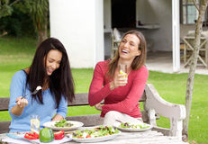 Two female friends laughing and having lunch together Royalty Free Stock Images