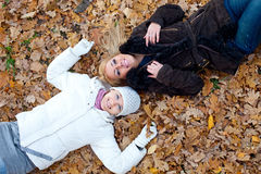 Two female friends lying down in autumn leaves Stock Image