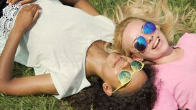 Two female friends lying on grass, gossiping about guys and smiling, friendship. Stock footage stock footage