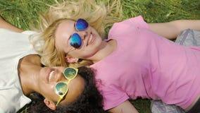 Two female friends lying on grass in park, enjoying summer weekend, friendship. Stock footage stock video footage