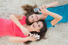 Two female friends lying on rug and text messaging Royalty Free Stock Images