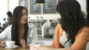 Two Female Friends Meeting In Busy Coffee Shop Stock Image