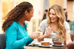 Two Female Friends Meeting In Cafe. Eating Snack Smiling At Each Other Royalty Free Stock Image