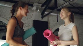 Two female friends are meeting in yoga studio, chatting emotionally and laughing. Spacious loft style wellness center. Two attractive female friends are meeting stock video