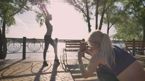 Two female friends in park taking photos, one of them standing and posing for camera, while other is holding phone, park. Near river stock video
