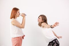 Two female friends playing with an action camera. In studio over a white wall Royalty Free Stock Photos