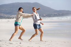 Two female friends playing on the beach Royalty Free Stock Photo