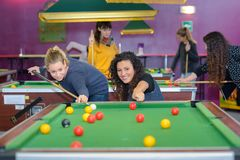 Two female friends playing billiards stock images