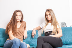 Two female friends posing in fashion style. On the couch in the house Royalty Free Stock Photo