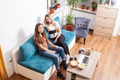 Two female friends posing in fashion style. On the couch in the house Stock Images