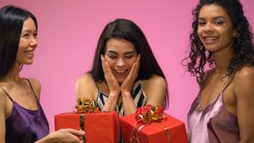 Two female friends presenting gifts to excited woman, bridal shower celebration