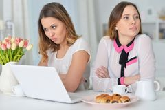 Two female friends after quarrel. Sitting at table with laptop Royalty Free Stock Photos
