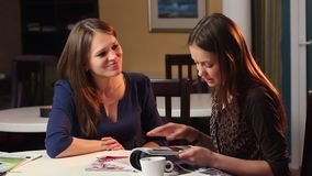 Two female friends read magazine laughing, girls company smile. Stock footage stock video