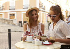Two female friends reading a guidebook outside a cafe, Ibiza Royalty Free Stock Image