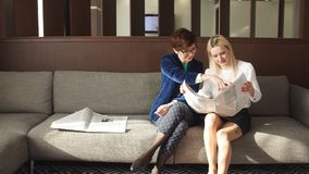 Two female friends reading newspaper news during sitting on a couch stock video footage