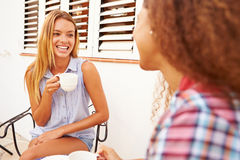 Two Female Friends Relaxing Outdoors And Drinking Coffee Stock Photography
