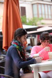 Two female friends relaxing over coffee. Sitting at a table in an outdoor restaurant smiling as they chat together Stock Images