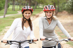 Two Female friends riding bikes in park Stock Photo