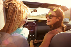 Two Female Friends On Road Trip Driving In Convertible Car Stock Image