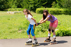 Two female friends roller skating Stock Photo