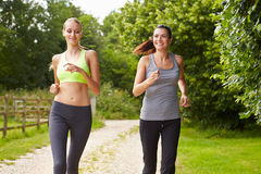 Two Female Friends On Run In Countryside Together Stock Photos