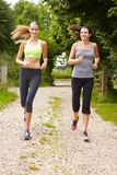 Two Female Friends On Run In Countryside Together Stock Image