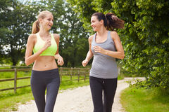 Two Female Friends On Run In Countryside Together Royalty Free Stock Photography