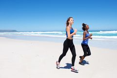 Two female friends running on beach Royalty Free Stock Images