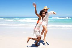 Two female friends running on beach together Royalty Free Stock Photo